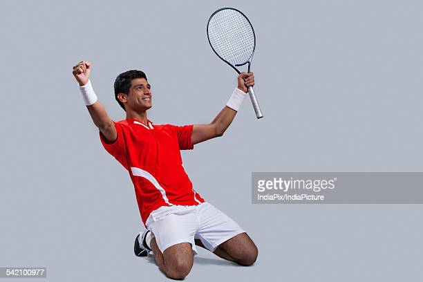 Happy male tennis player celebrating victory isolated over gray background