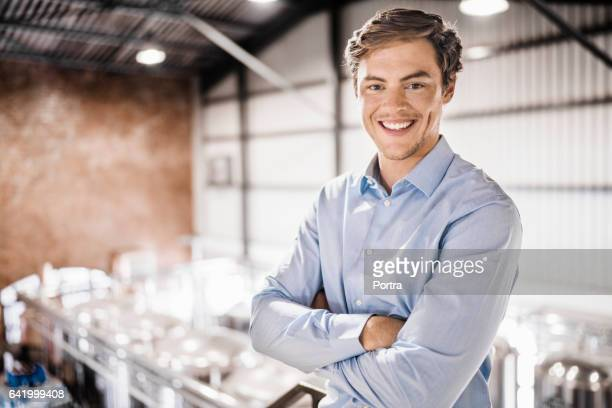 Happy male worker standing arms crossed in brewery