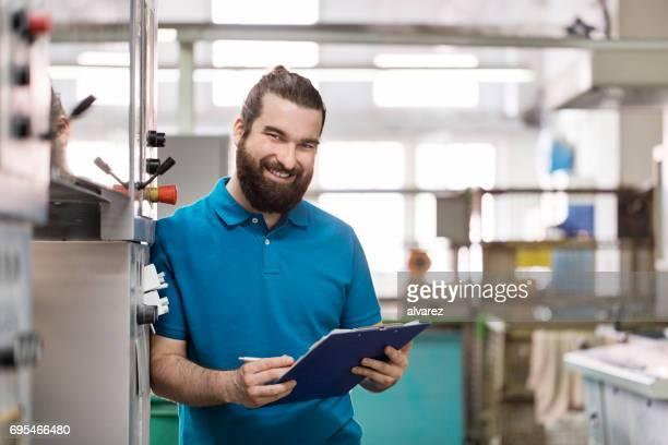 glücklich männlichen arbeitnehmer mit zwischenablage am druckerei. - klemmbrett stock-fotos und bilder