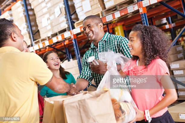 Happy man and daughter making donations at a food pantry