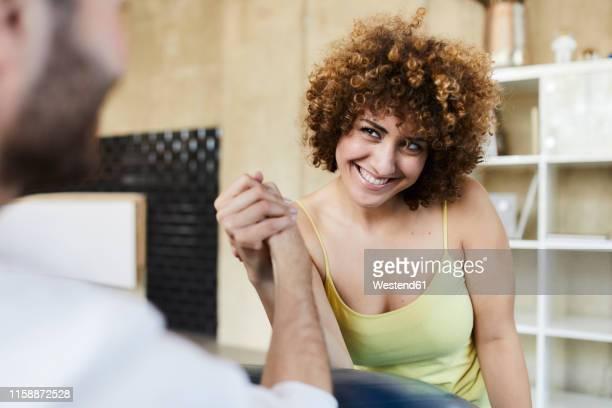 happy man and woman arm wrestling in office - wettbewerb konzepte stock-fotos und bilder
