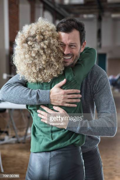 Happy man and woman hugging in office