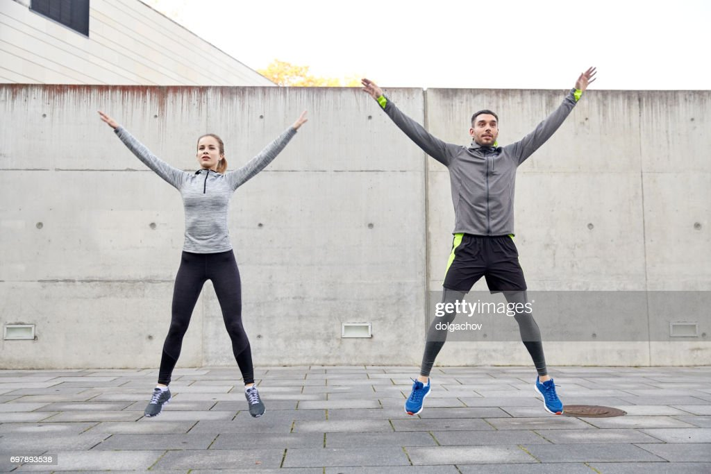 happy man and woman jumping outdoors : Stock Photo