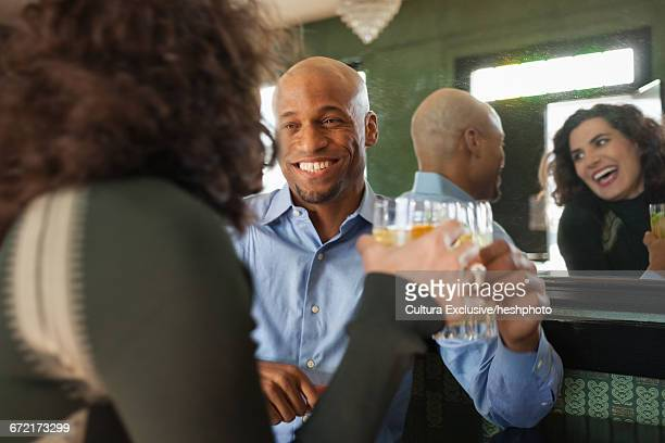 happy man and woman making a toast in recreational bar - heshphoto stock pictures, royalty-free photos & images