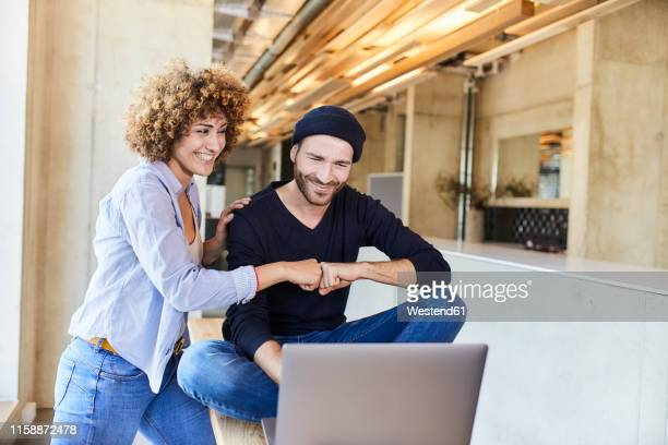 happy man and woman with laptop fist bumping in modern office - good news stock pictures, royalty-free photos & images