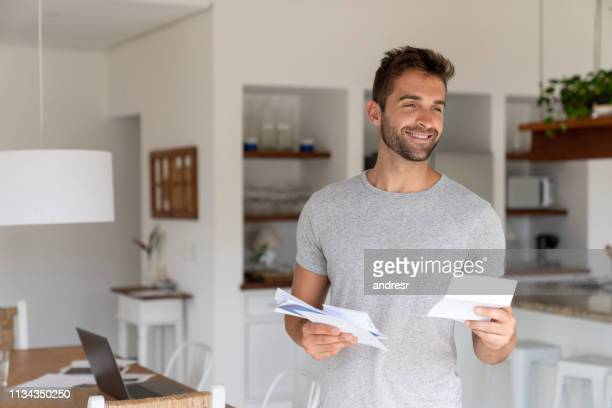 homem feliz em casa que verific o correio - responder - fotografias e filmes do acervo