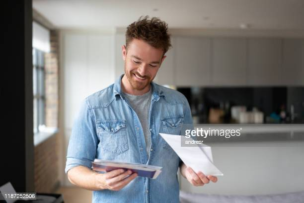 happy man at home checking the mail - sending stock pictures, royalty-free photos & images