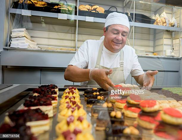 happy man baking sweet treats - happy merchant stock pictures, royalty-free photos & images