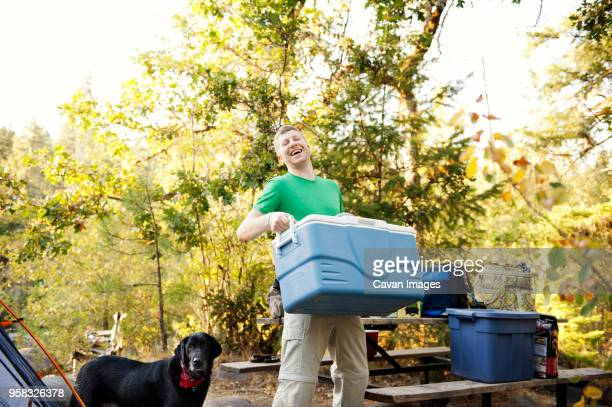happy man carrying cooler while standing by dog at campsite - esky stock photos and pictures