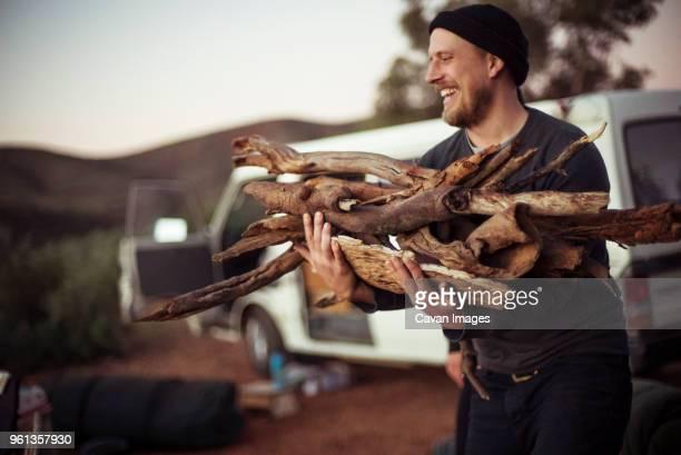 happy man carrying firewood against van on field - 薪 ストックフォトと画像