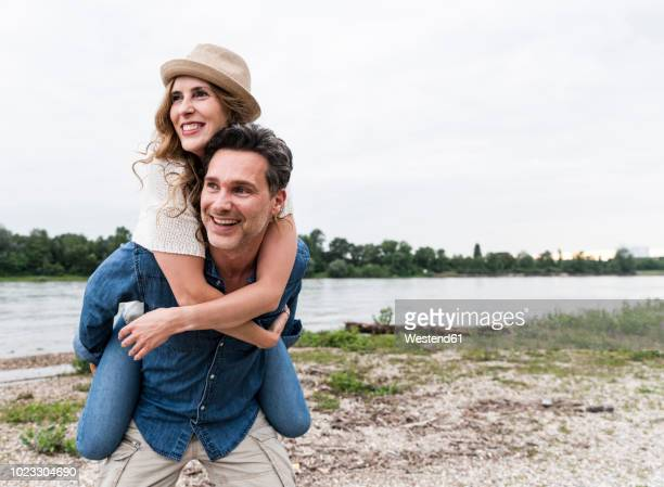 happy man carrying girlfriend piggyback at the riverside - couples stock pictures, royalty-free photos & images
