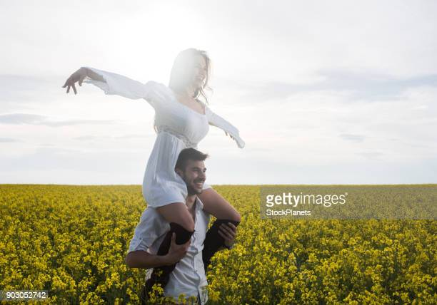 happy man carrying his girlfriend on shoulders in a field of yellow flowers. - carrying a person on shoulders stock photos and pictures