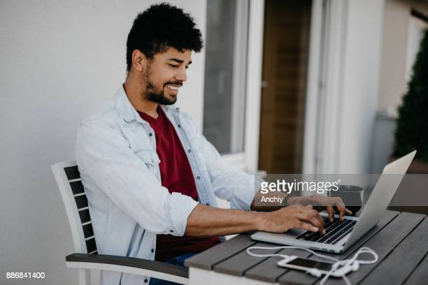 Happy man chilling on the terrace and using computer to chat with friends on social network.
