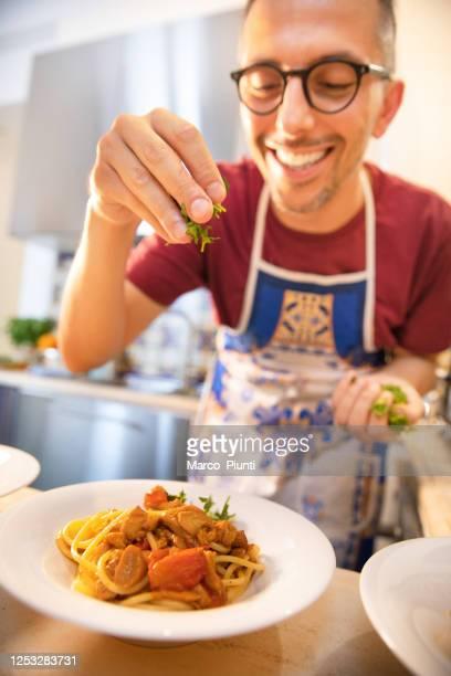happy man cooking pasta italiaanse spaghetti - italiaanse cultuur stockfoto's en -beelden