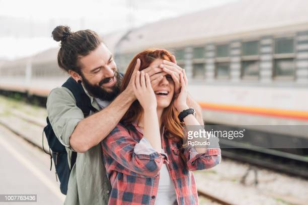 Happy man covering his girlfriend's eyes and looking at her