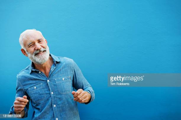 happy man dancing next to blue wall, outside - vitality stock pictures, royalty-free photos & images