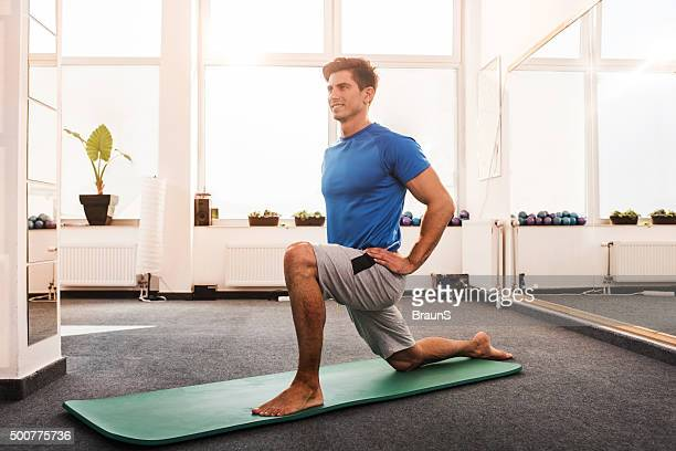 Happy man doing stretching exercises in a health club.