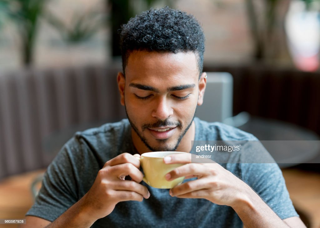 Happy man drinking a cup of coffee at a cafe : Stock Photo