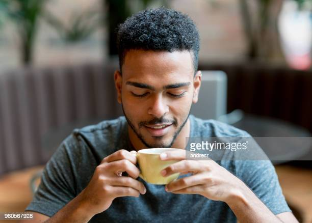 happy man drinking a cup of coffee at a cafe - espresso stock photos and pictures