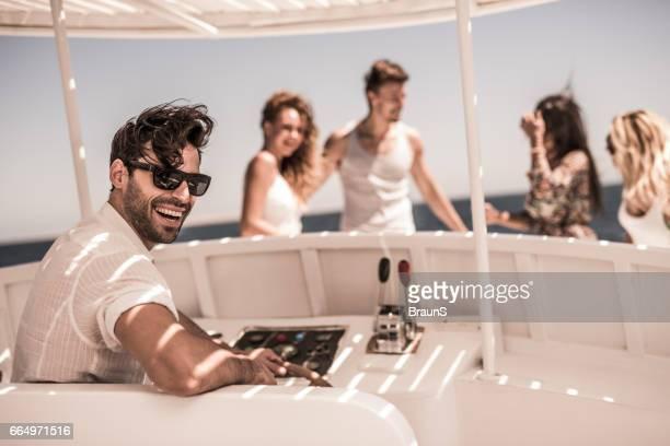 Heureux homme au volant d'un bateau avec ses amis.