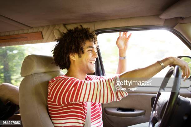 Happy man driving car on sunny day