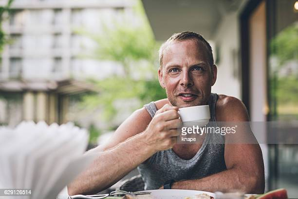 Happy man eating healthy breakfast outdoors