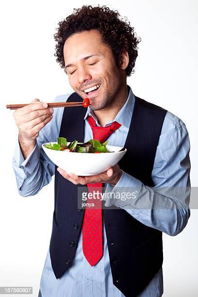 Heureux homme manger une salade avec chop bâtons
