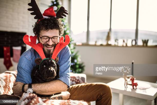 happy man embracing cute dog - antler stock pictures, royalty-free photos & images