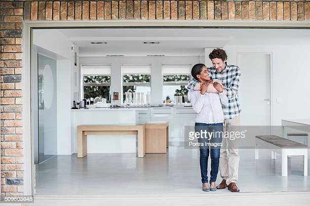 Happy man embracing woman at home