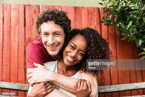 happy man embracing woman at yard - multiracial couple stock photos and pictures