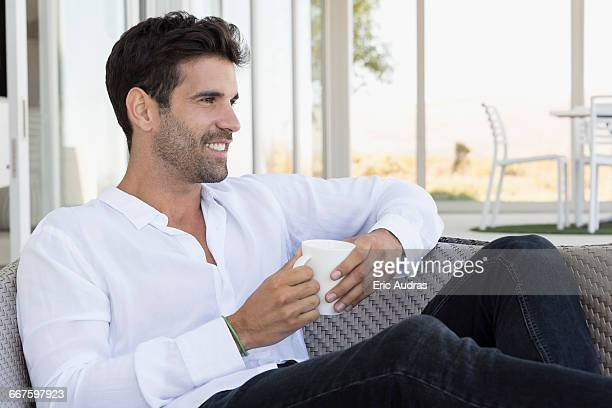 Happy man enjoying a cup of coffee at home