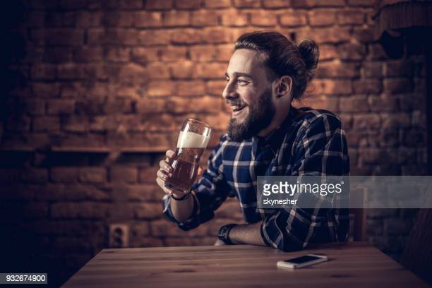 happy man enjoying in beer while sitting in a bar. - one man only stock pictures, royalty-free photos & images