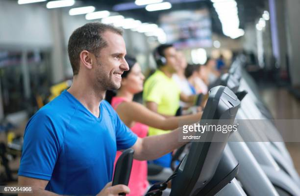 Happy man exercising at the gym on a cross trainer