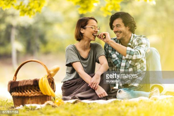 Happy man feeding his girlfriend at picnic during springtime.