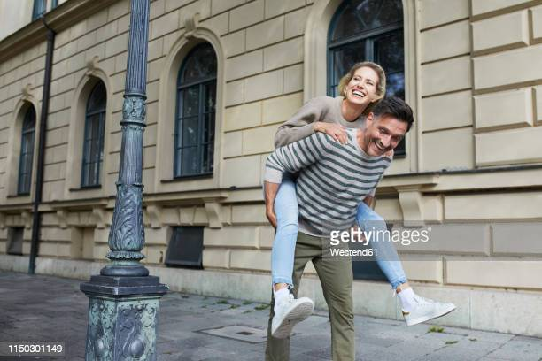 happy man giving woman piggyback ride on pavement in the city - piggyback stock pictures, royalty-free photos & images