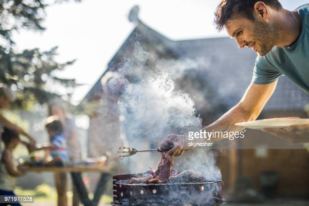 happy man grilling meat on a barbecue grill outdoors. - incidental people stock pictures, royalty-free photos & images