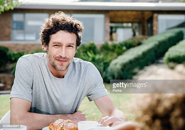 happy man having breakfast at outdoor table - mid adult men stock-fotos und bilder