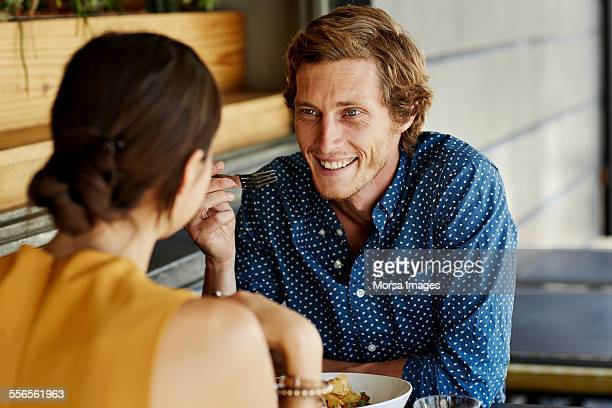 happy man having food with woman at restaurant - man eating woman out - fotografias e filmes do acervo