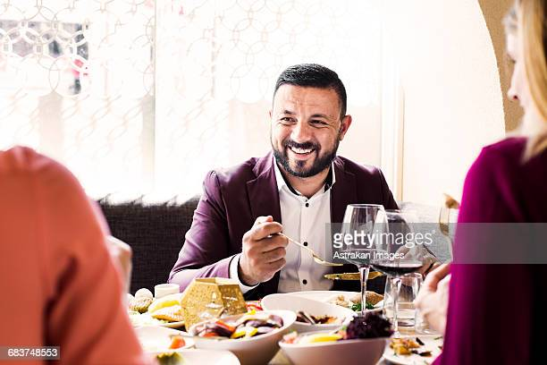 Happy man having meze with friends at Lebanese restaurant