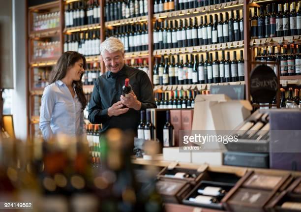 Glücklicher Mann hält eine Flasche Wein und Fragen an die Verkäuferin in einem Weingut