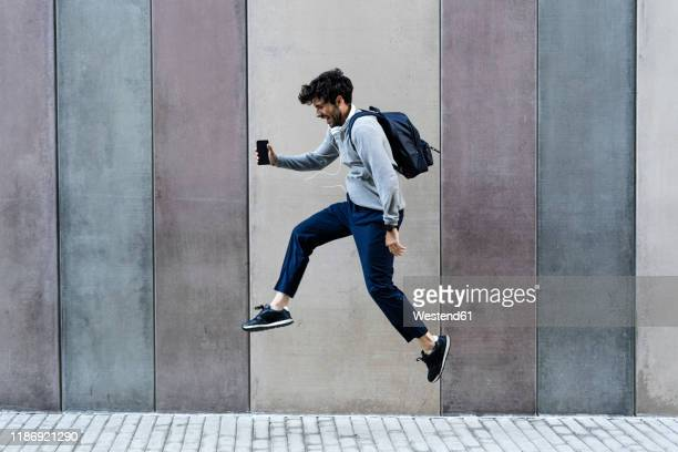 happy man holding cell phone jumping in front of a wall - saltar imagens e fotografias de stock