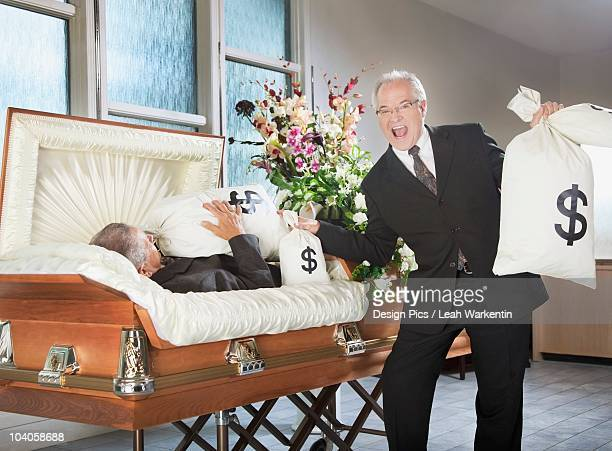 A Happy Man Holds Bags Of Money Beside A Deceased Man In A Coffin