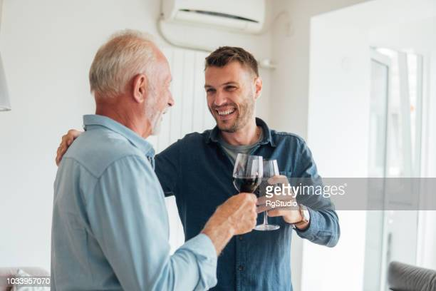 Happy man hugging his father and having a wine
