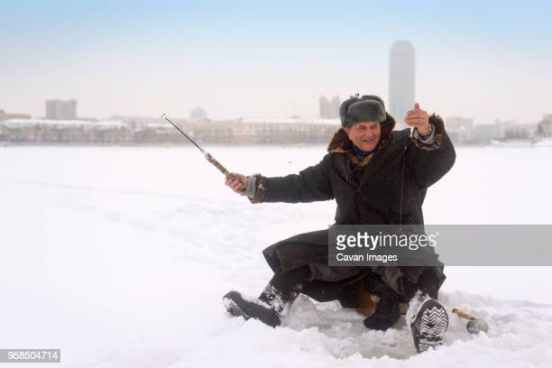 happy man ice fishing in frozen lake - ice fishing stock pictures, royalty-free photos & images
