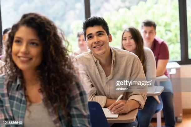 gelukkig man in een klaslokaal met een groep van studenten - latijns amerikaanse en hispanic etniciteiten stockfoto's en -beelden