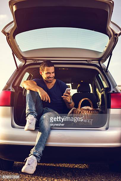 Happy man in car trunk texting on cell phone.