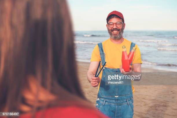 Happy man in dungarees on the beach offering soft drink to woman