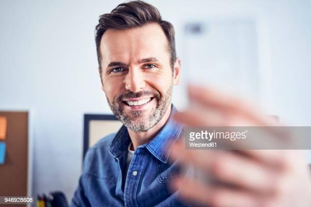 Happy man in office taking selfie