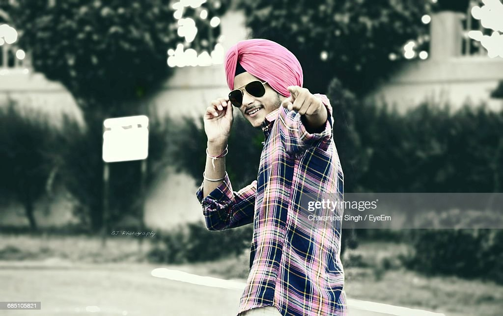 Happy Man In Turban And Sunglasses Pointing Finger While Standing On Street
