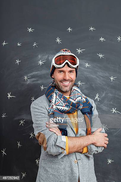 happy man in winter outfit against blackboard - izusek stock pictures, royalty-free photos & images